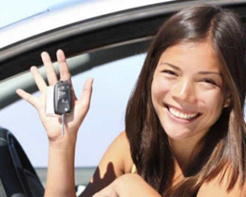 Una ragazza sorride dentro un'auto con una chiave in mano