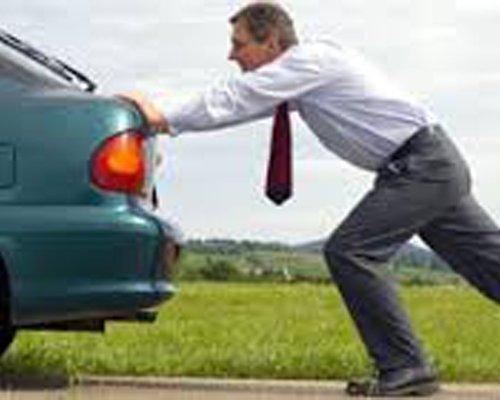 Un uomo in camicia e cravatta spinge un'auto in panne
