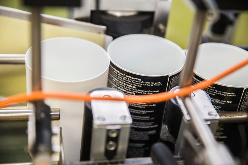 Vista del macchinario con dei vasetti durante la fase di etichettatura