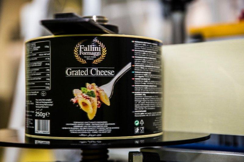 Una latta di formaggio grattuggiato sopra a una tortiera