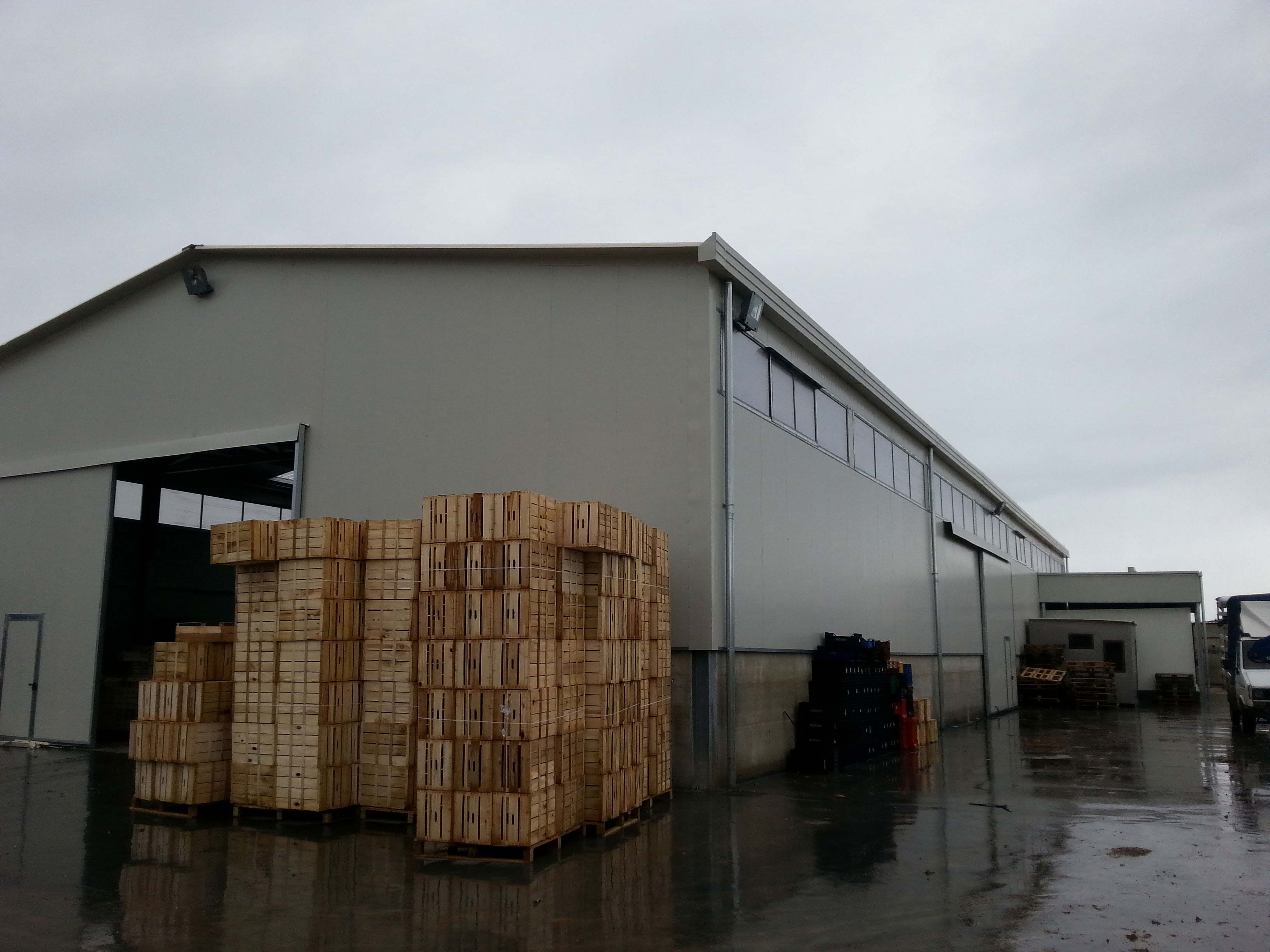 esterno dello stabile con una serie di scatoloni in legno su dei bancali