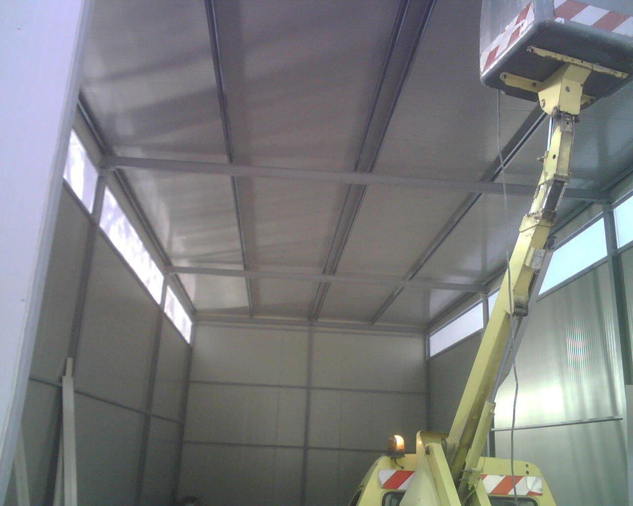 interno di un magazzino con struttura in ferro per coperture industriali e un camioncino giallo con un braccio elevatore