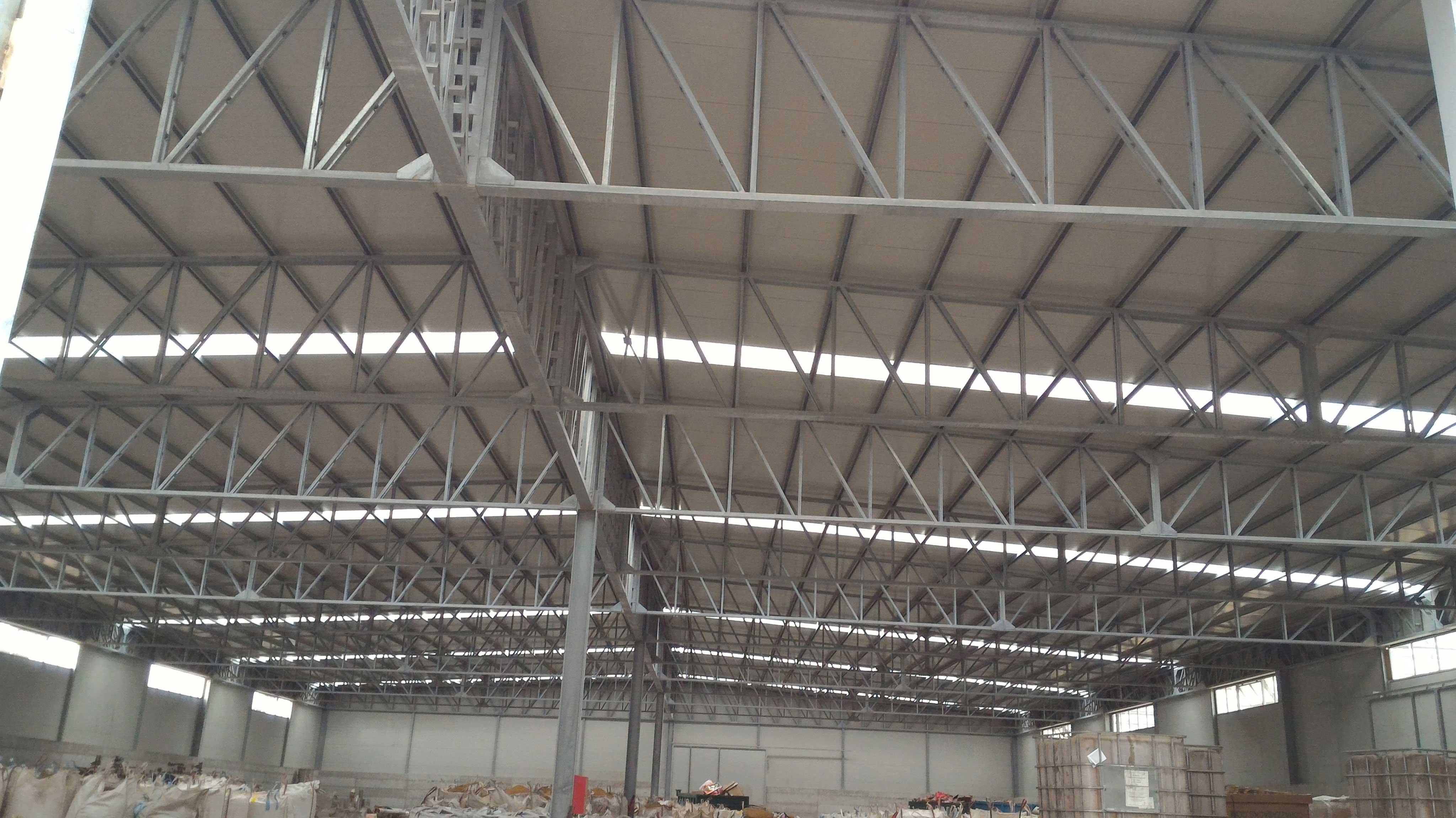Delle travi in ferro all'interno dello stabile che sorreggono la copertura industriale