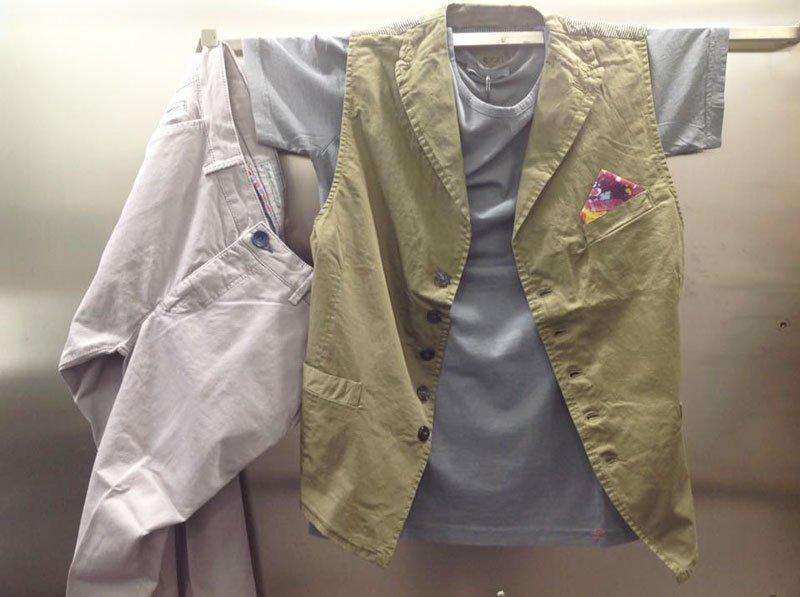 un paio di pantaloni bianchi, una t shirt grigia e un gilet verde pisello appesi al muro