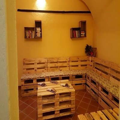 una panca angolare e un tavolino fatti di casse di legno