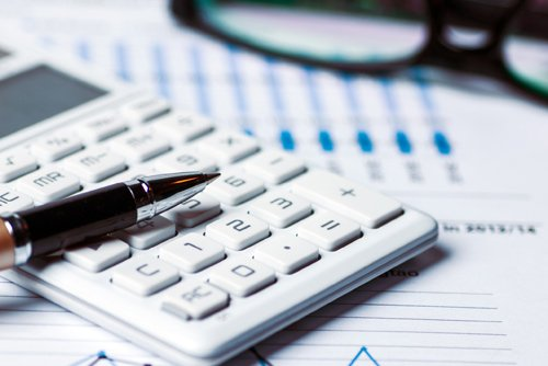 calculator and pen on financial forecasts