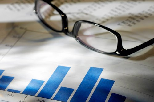 a pair of glasses on top of financial charts
