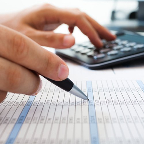 man calculates tax with calculator and pen