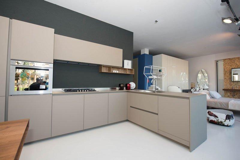cucina moderna angolare  di color grigio e sulla destra si intravede un letto con un cuscino