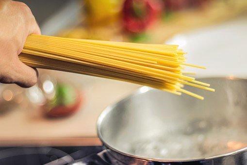 una mano con degli spaghetti in mano e accanto una pentola in acciaio con dell'acqua che bolle