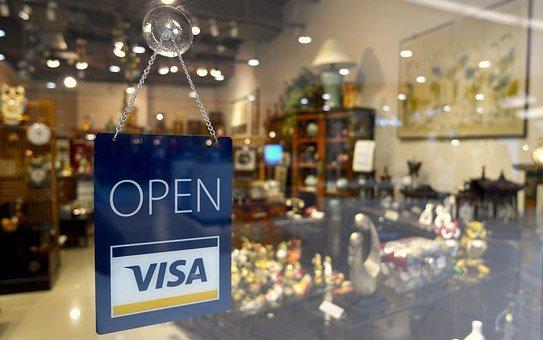 vetrina di un negozio con dei mobili in legno e scritta Open Visa sul vetro