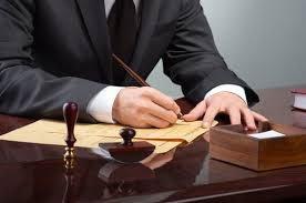 un uomo con giacca e cravatta a una scrivania mentre scrive su un foglio