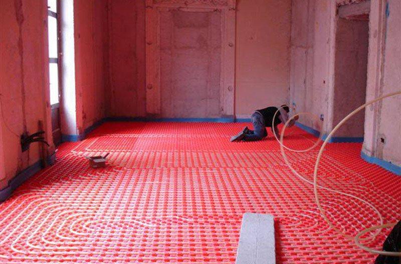 un uomo al lavoro su un impianto sul pavimento