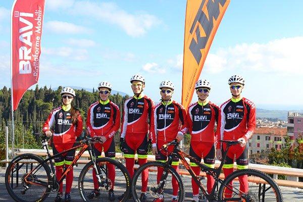 dei ciclisti in posa per una foto con delle tute nere e rosse e una bicicletta