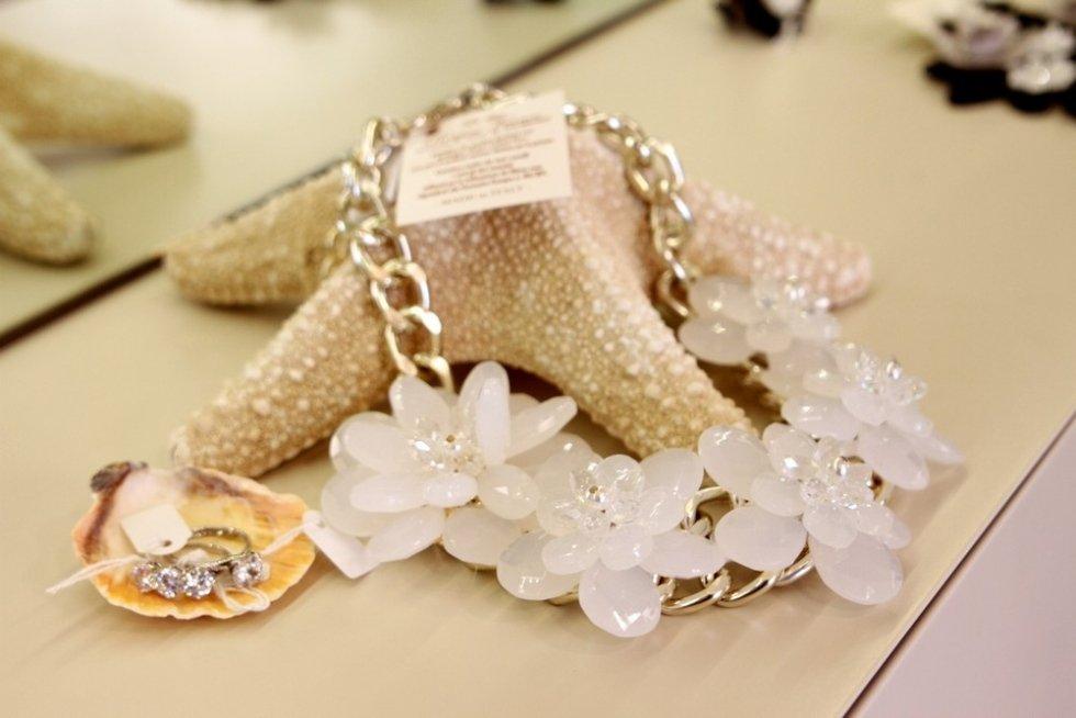 un bracciale con una catena e dei fiori bianchi