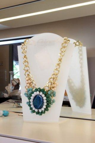 una collana con una catena dorata e un fiore di color verde