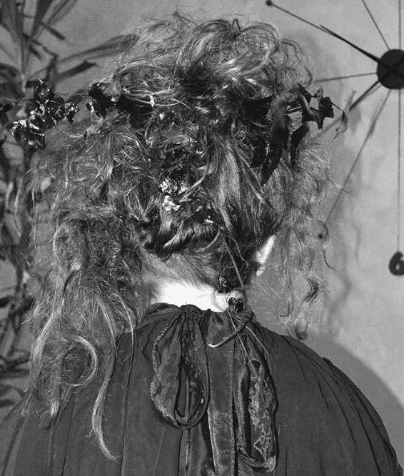 un'immagine in bianco e nero di una donna con capelli ricci vista da dietro