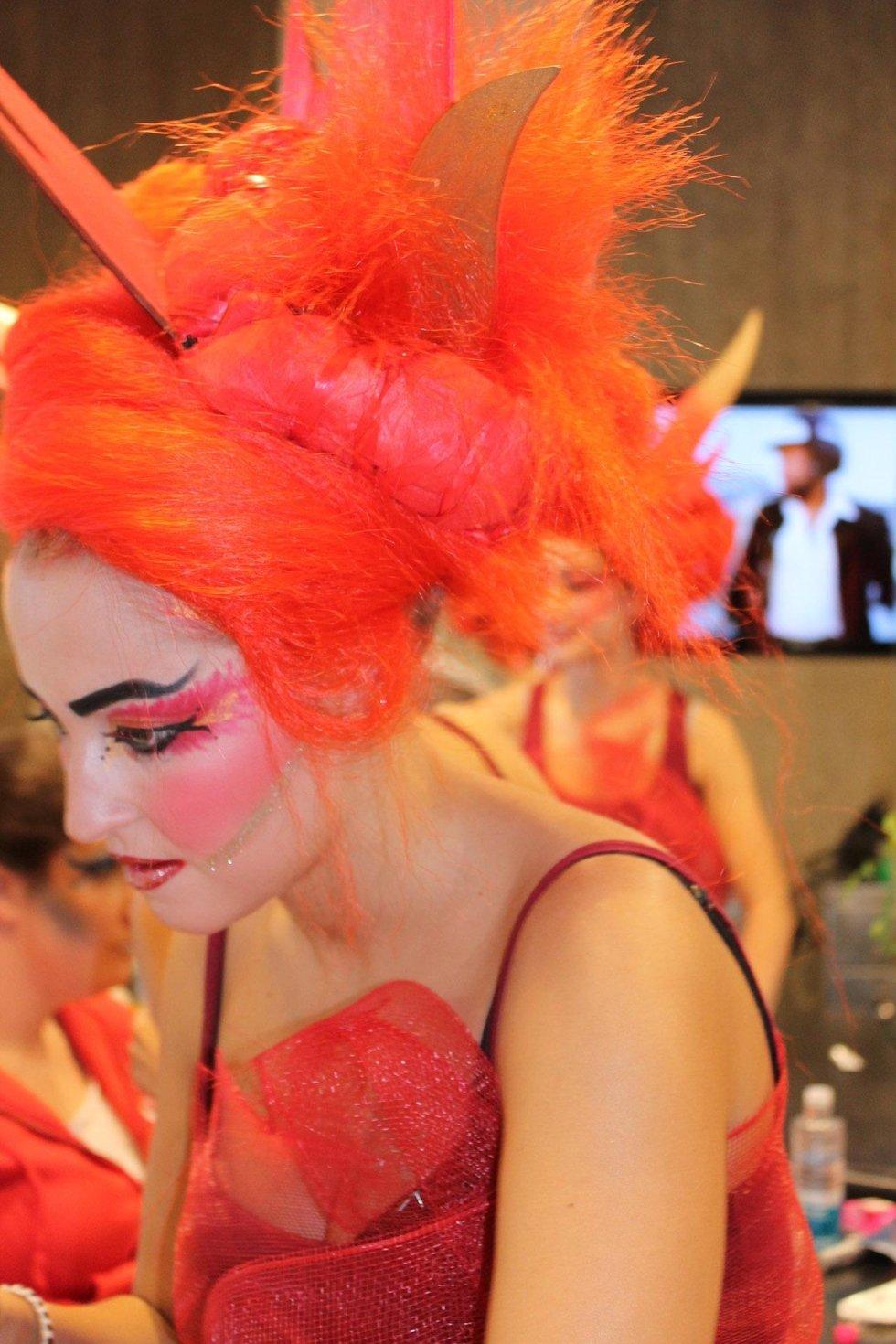 una donna con un vestito rosso e una parrucca arancione