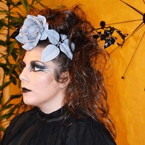 una donna con fiori blu in testa e rossetto nero