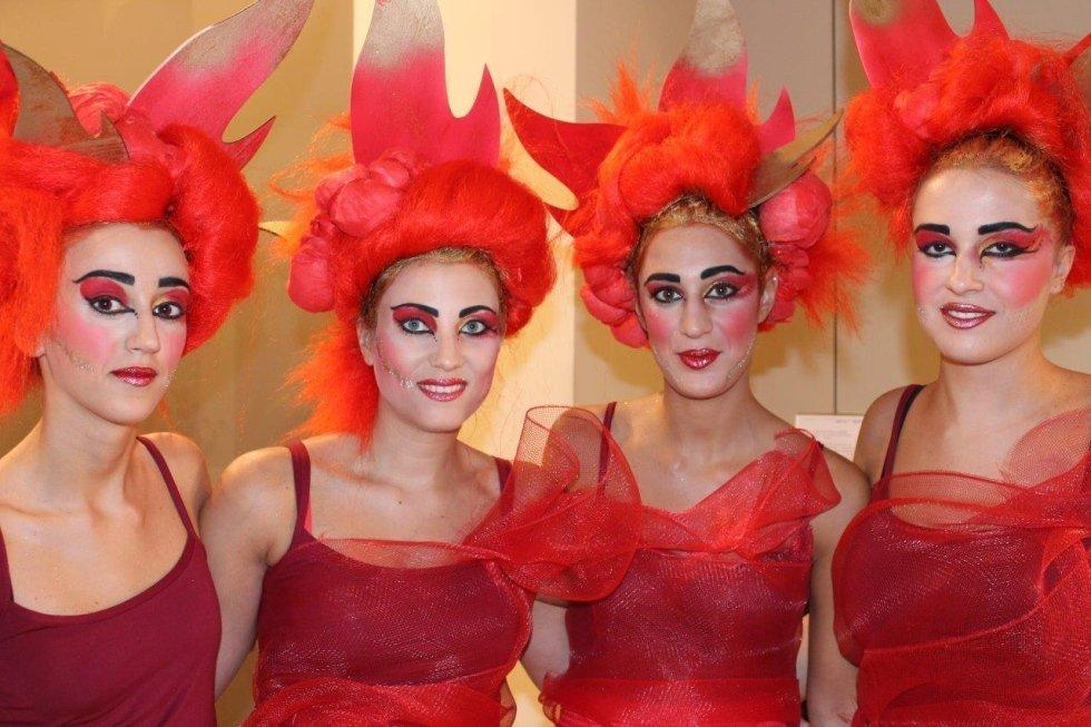 delle ragazze con delle parrucche arancioni e abiti rossi