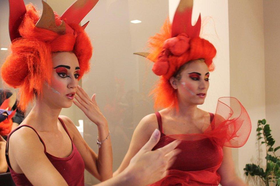 due ragazze  con delle parrucche arancioni e abiti rossi