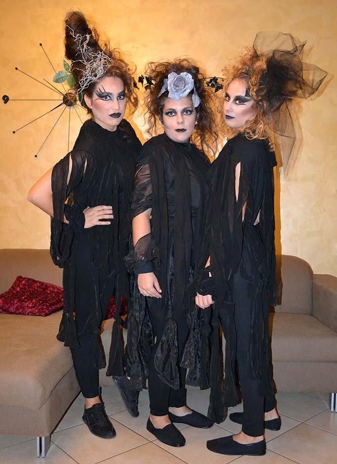 tre ragazze con degli  abiti neri e viso truccato da strega