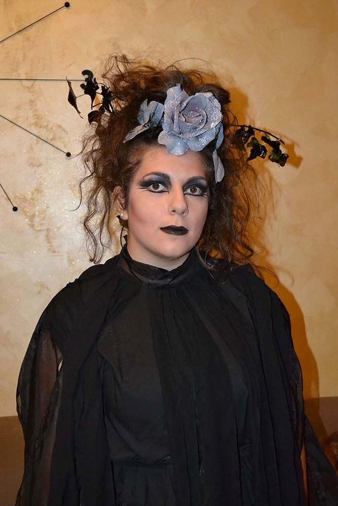 una donna con un abito nero e il  viso truccato da stega