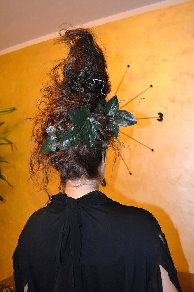 i capelli di una donna tirati in su con la lacca e delle foglie in testa