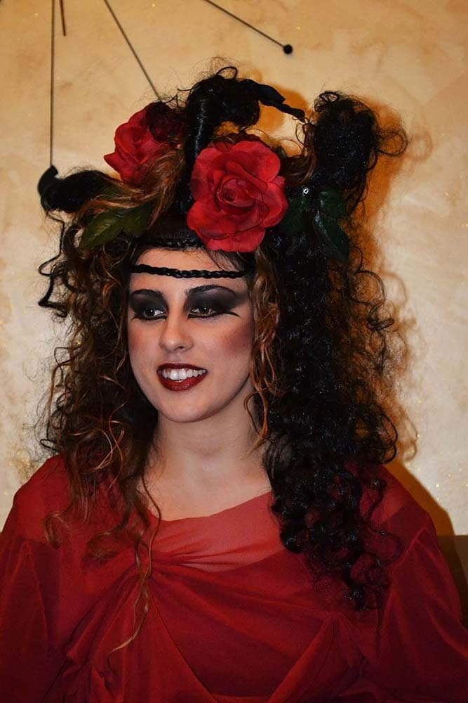 una donna con un trucco dark, capelli ricci e abito rosso