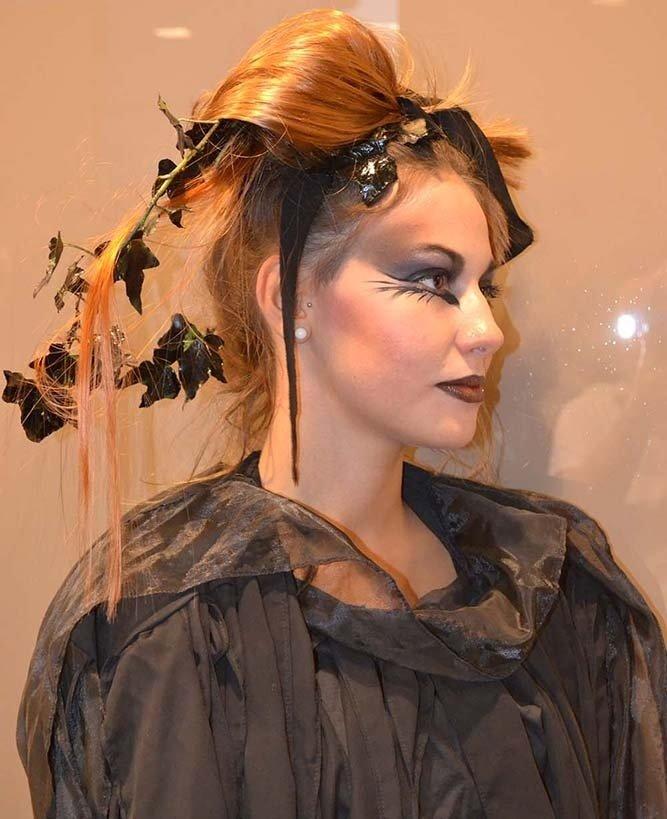 una donna con capelli arancioni con delle foglie e un trucco dark
