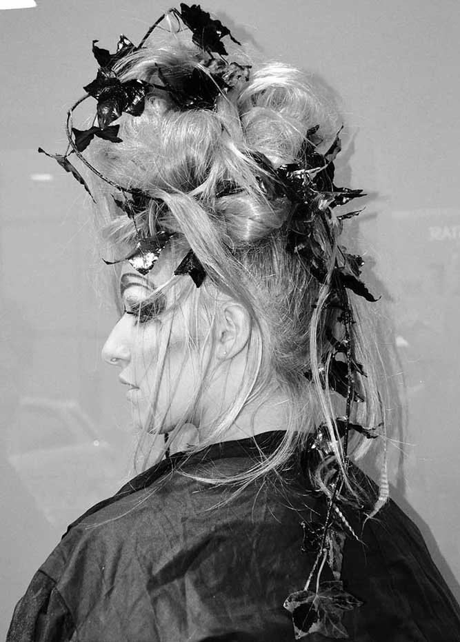 foto in bianco e nero di una donna con capelli in su, delle foglie e trucco dark