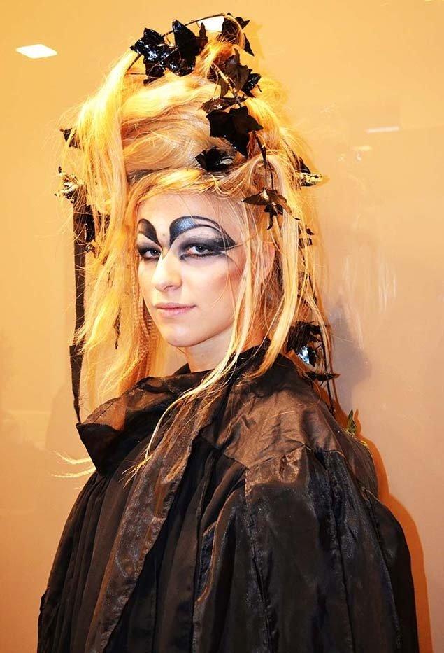 una donna con capelli in su con delle foglie e trucco dark
