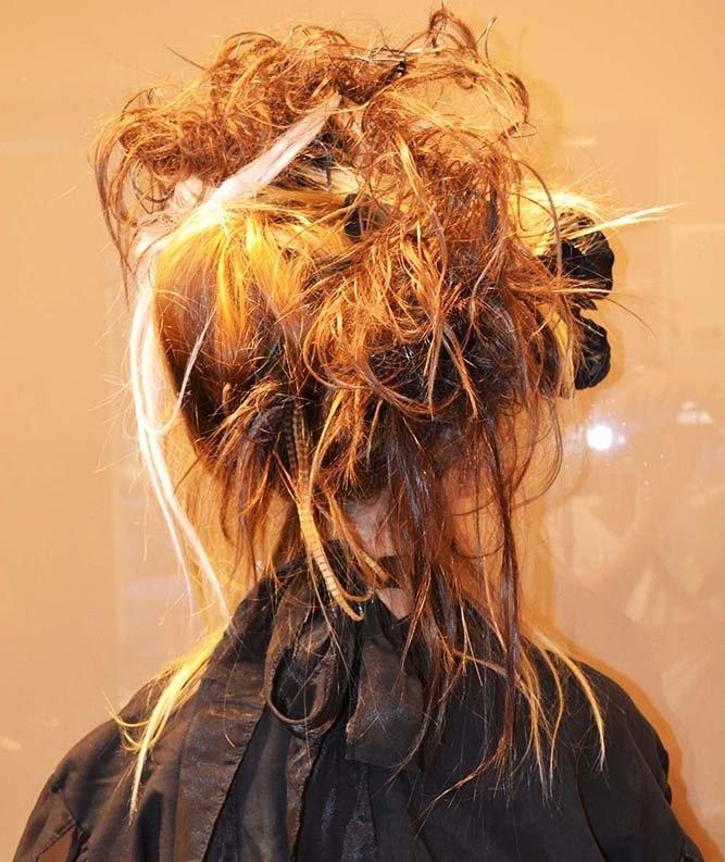 una donna con capelli arancioni mossi e raccolti vista nda dietro