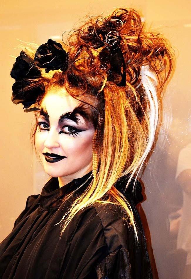 una donna con un trucco dark e capelli arancioni con delle foglie