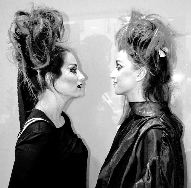 Due donne con acconciature gotiche che si guardano negli occhi