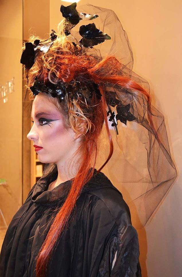 Donna bionda con trucco pesante, ciocche rosse e velo nero tra i capelli