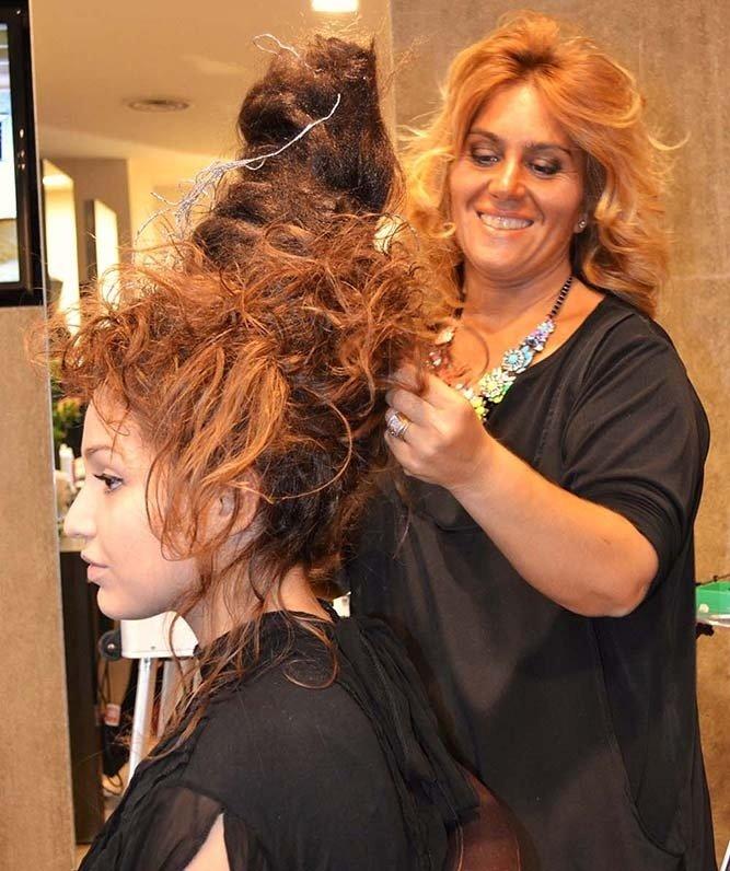 Parrucchiera mentre realizza un'acconcaitura a una ragazza con capelli rossi