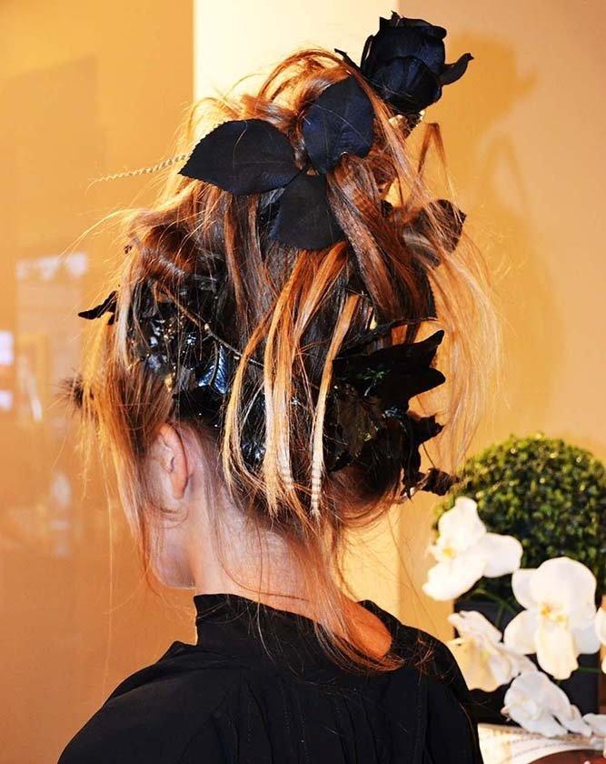 Donna con acconciatura gotica con rose e petali neri tra i capelli