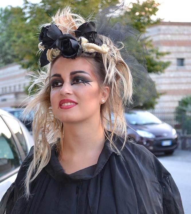 Ragazza bionda con orecchini di perla e rose nere tra i capelli