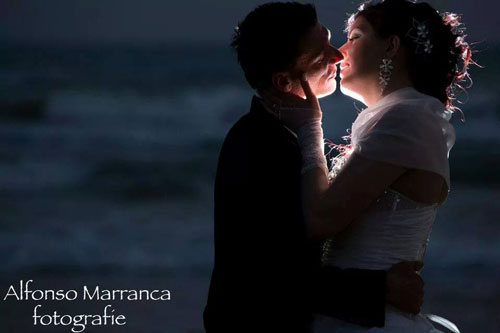Coppia con la luce dopo di loro, che si baciano di fronte al mare
