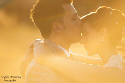 Marito baciando in fronte a sua moglie , il sole loro illumina