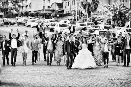 Foto in bianco e nero dei neo novelli camminando per la strada mano le mani, la famiglia e gli amici dopo di loro