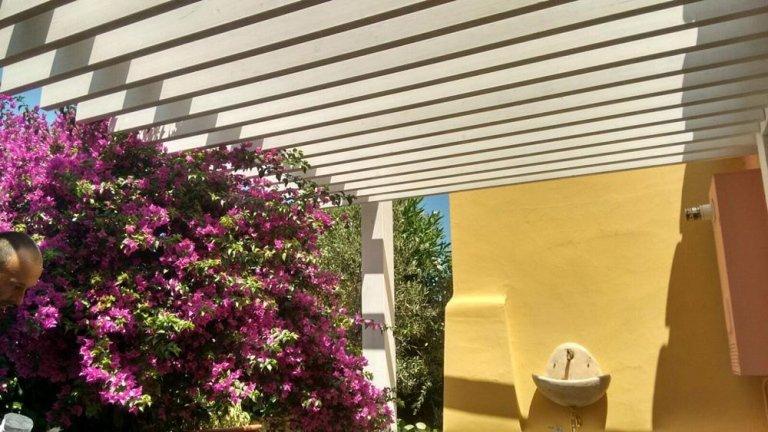 uno stabile di color rosa e una struttura a pilastri di color bianco su un balcone