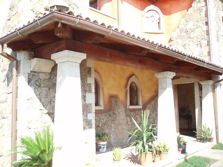 una palazzina color sabbia e sopra il terrazzo una struttura con una tettoia
