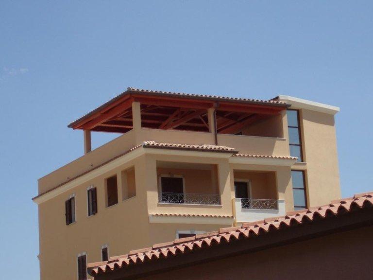 una rete in plastica rossa di una zona cantiere e più avanti una struttura con dei pilastri e una tettoia