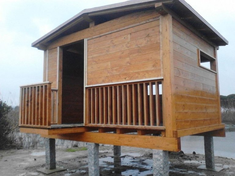 una casetta bianca con una finestrella e un tetto in legno