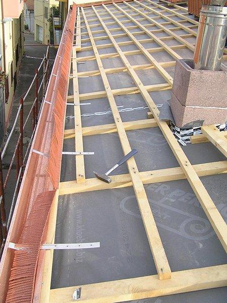 delle liste di legno in un tetto di uno stabile e un martello