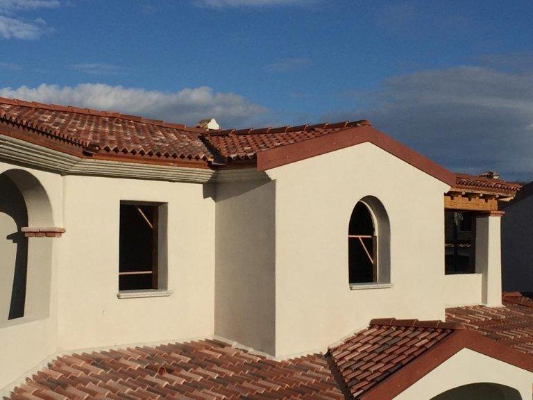 vista di una casa bianca con tetti ultimati e sulla sinistra su in terrazzino dei mattoni bianchi per terra