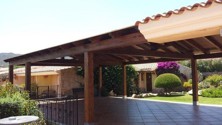 una piscina e in lontananza due strutture con dei pilastri in legno e dei tetti
