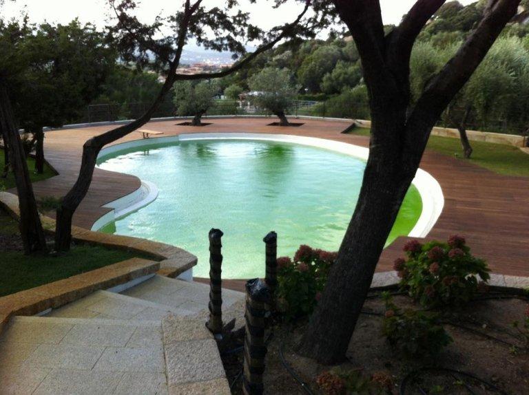 una piscina con bordo piscina in mattoni arancioni e legno con dei parapetti e dietro vista del cielo e del mare